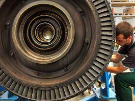 Man working on gas turbine in German factory (© AP Images)
