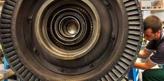 Man working on gas turbine in German factory (© AP Images)