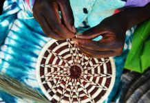 Hands weaving basket (© AP Images)