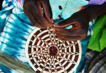 Manos tejiendo un cesto (© AP Images)