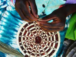 Hands weaving basket (© AP Images)
