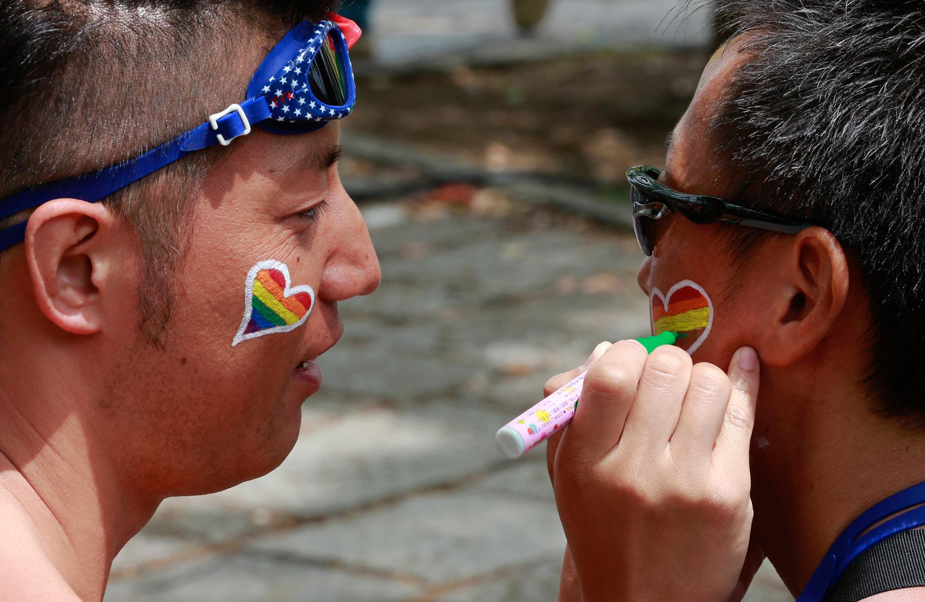 Homem pinta coração em formato de arco-íris no rosto de outro homem (© AP Images)