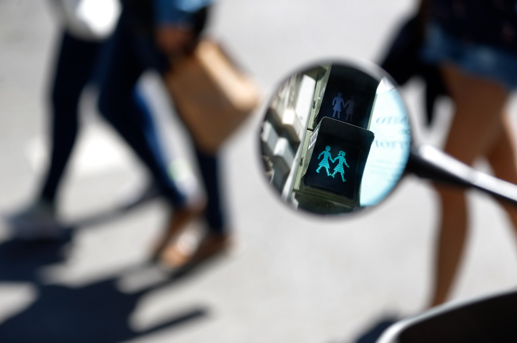 Traffic light reflected in mirror and displaying symbols for two women holding hands (© AP Images)