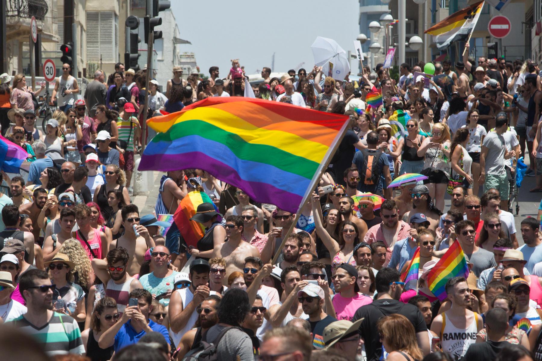 Pessoas desfilam com uma bandeira de arco-íris (© AP Images)