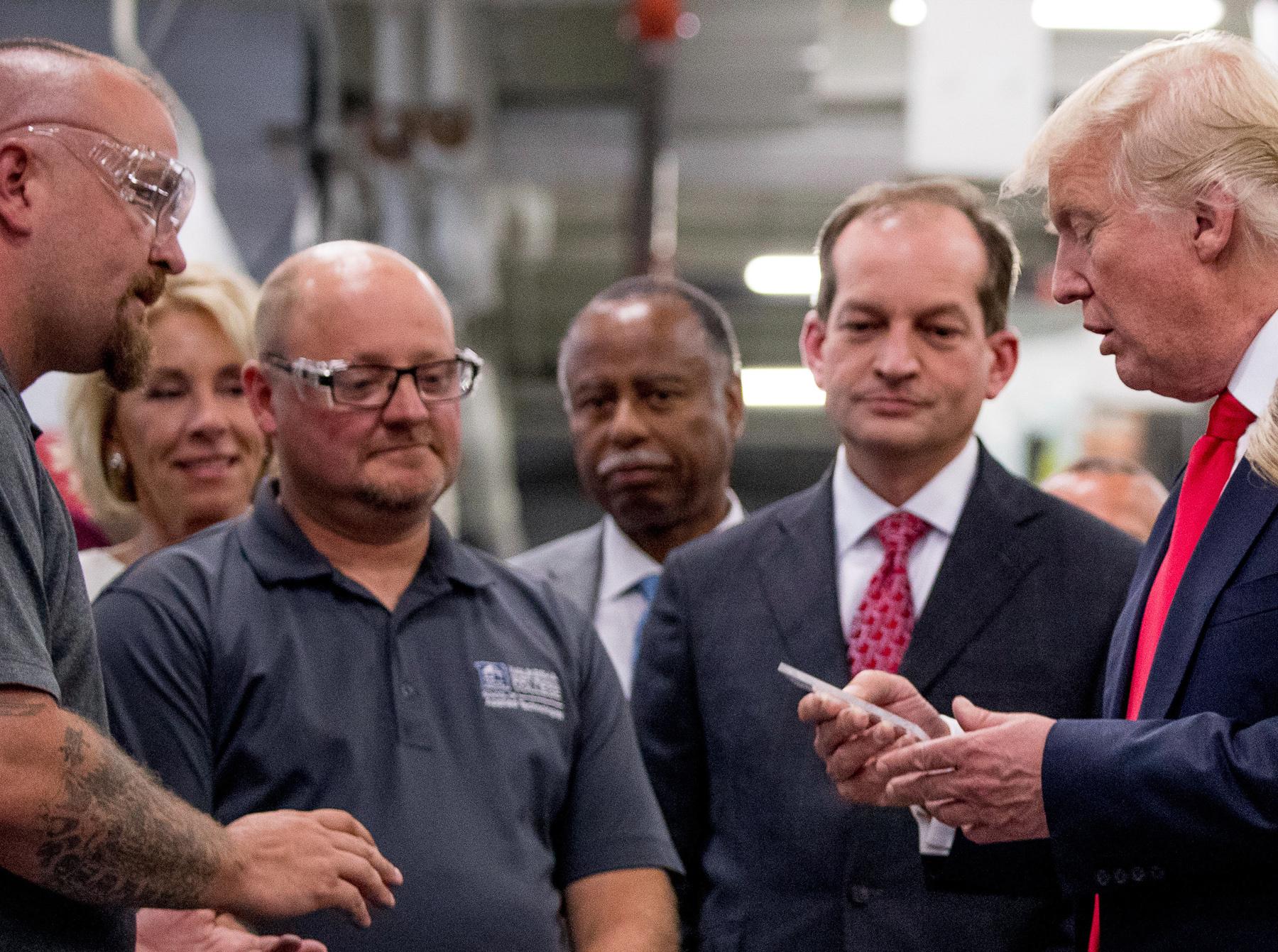 O presidente Trump se reúne com homens em uma fábrica (© AP Images)