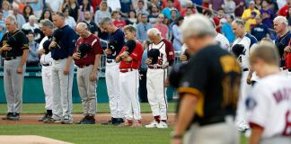 People bowing their heads on baseball field (© AP Images)