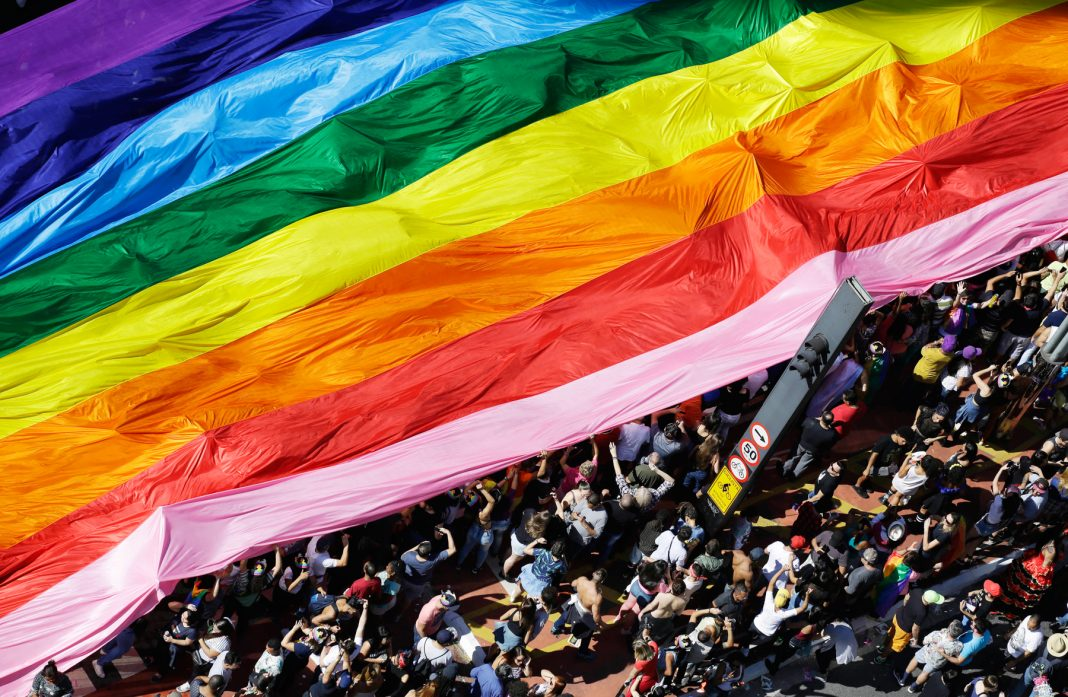 Parade participants carrying a rainbow flag (© AP Images)