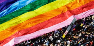 Parade participants carrying a rainbow flag (© AP Images)