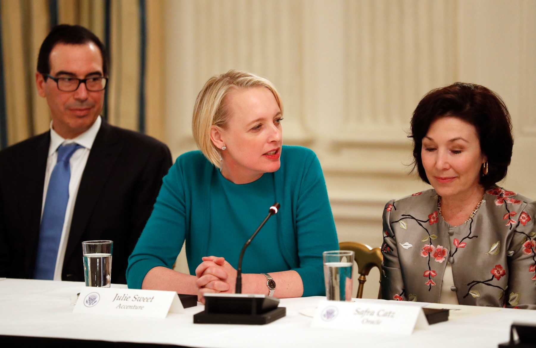 Steve Mnuchin seated with Julie Sweet (center) and Safra Catz (right) (© AP Images)