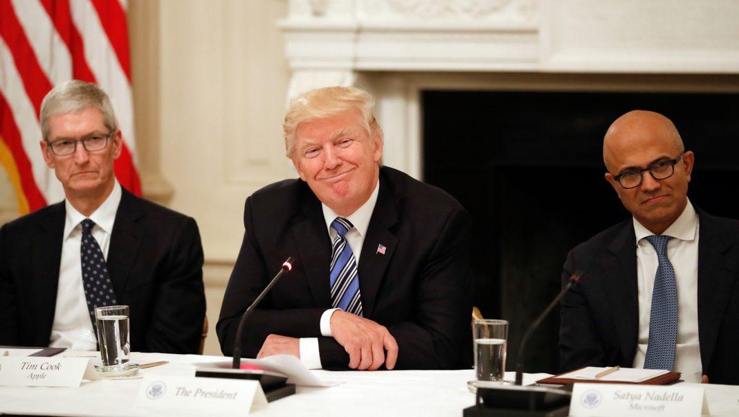 Tim Cook, el presidente Trump y Satya Nadella sentados a la mesa (© AP Images)