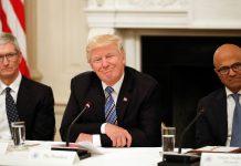 Tim Cook, presidente Trump e Satya Nadella sentados à mesa (© AP Images)