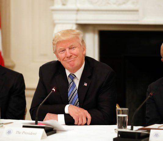 Tim Cook, President Trump and Satya Nadella sitting at table (© AP Images)