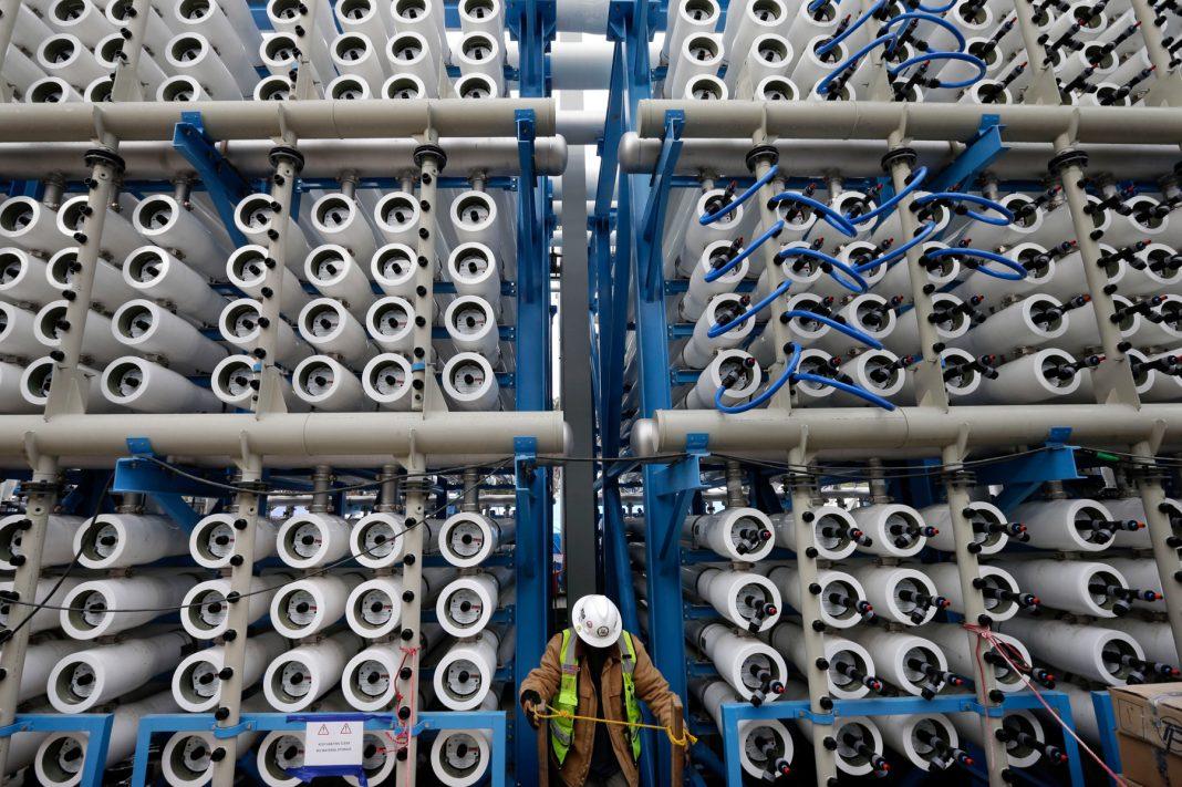 Un ouvrier inspecte une usine de dessalement par « osmose inversée » qui transforme de l'eau de mer en 189 millions de litres d'eau potable par jour en Californie (© AP Images)