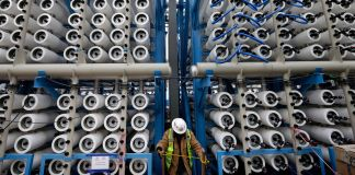 Person in safety gear between floor-to-ceiling racks of pipes (© AP Images)