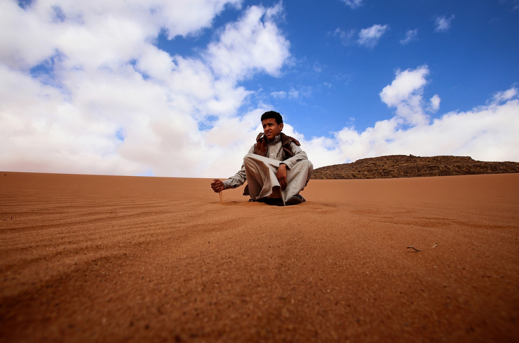 Teenage boy sitting in desert (© AP Images)