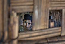 Adolescente en train de regarder par une ouverture dans une maison en bois (© AP Images)