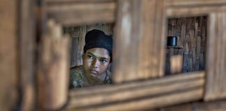 Teenager seen through a window of wooden house (© AP Images)