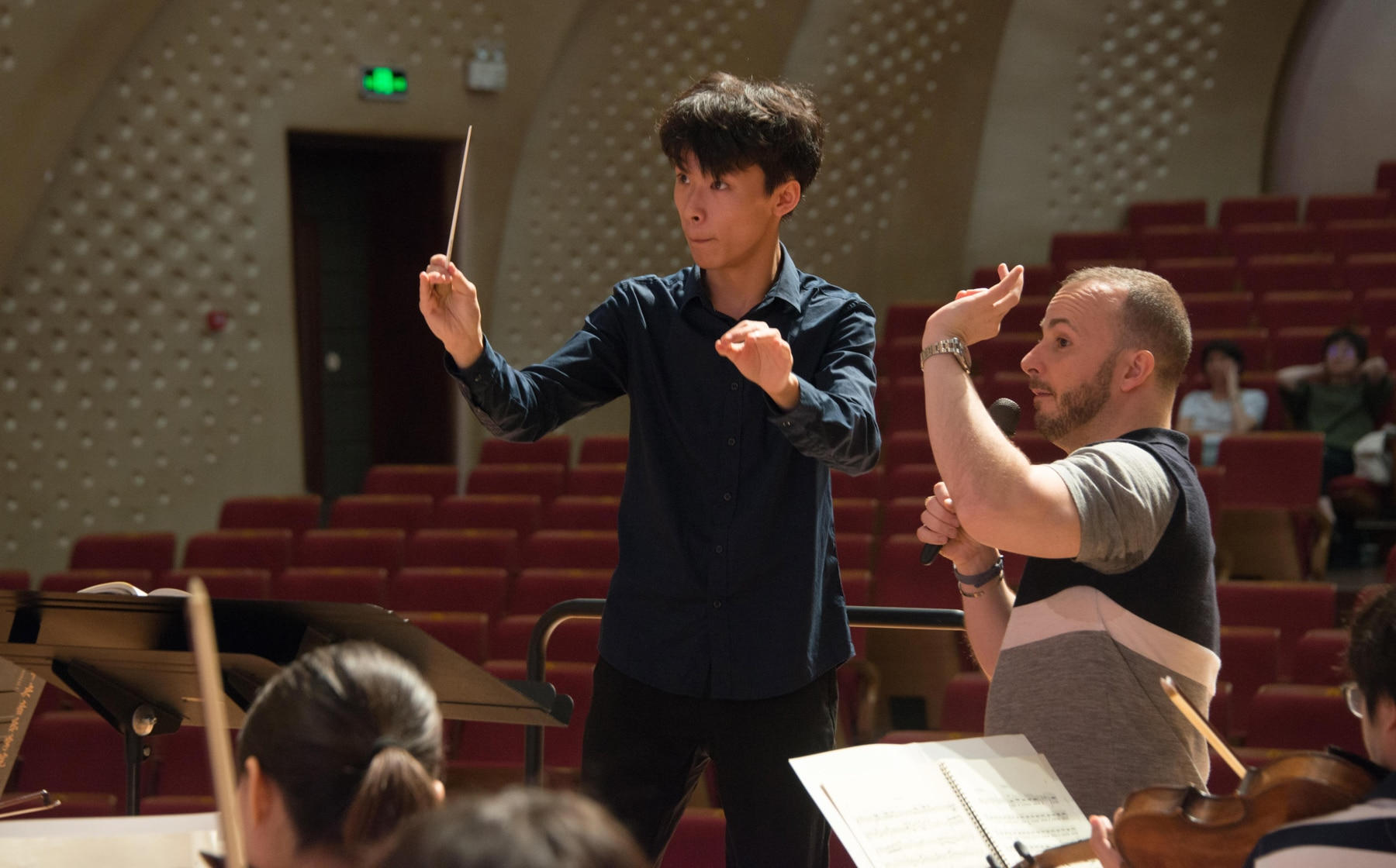 Young man gesturing with baton, another man directing him (Philadelphia Orchestra)
