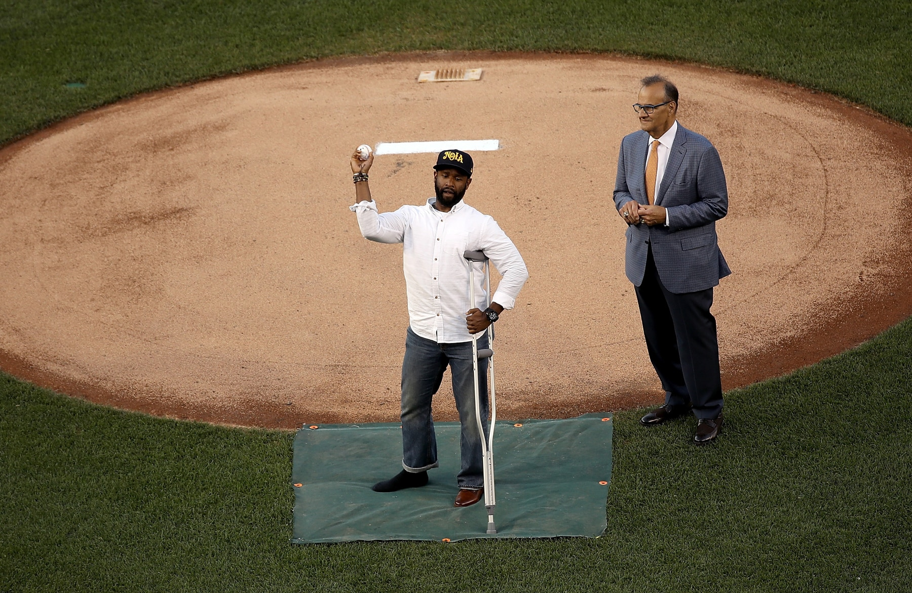 Man with crutch throwing baseball from near pitcher's mound (© Getty Images)