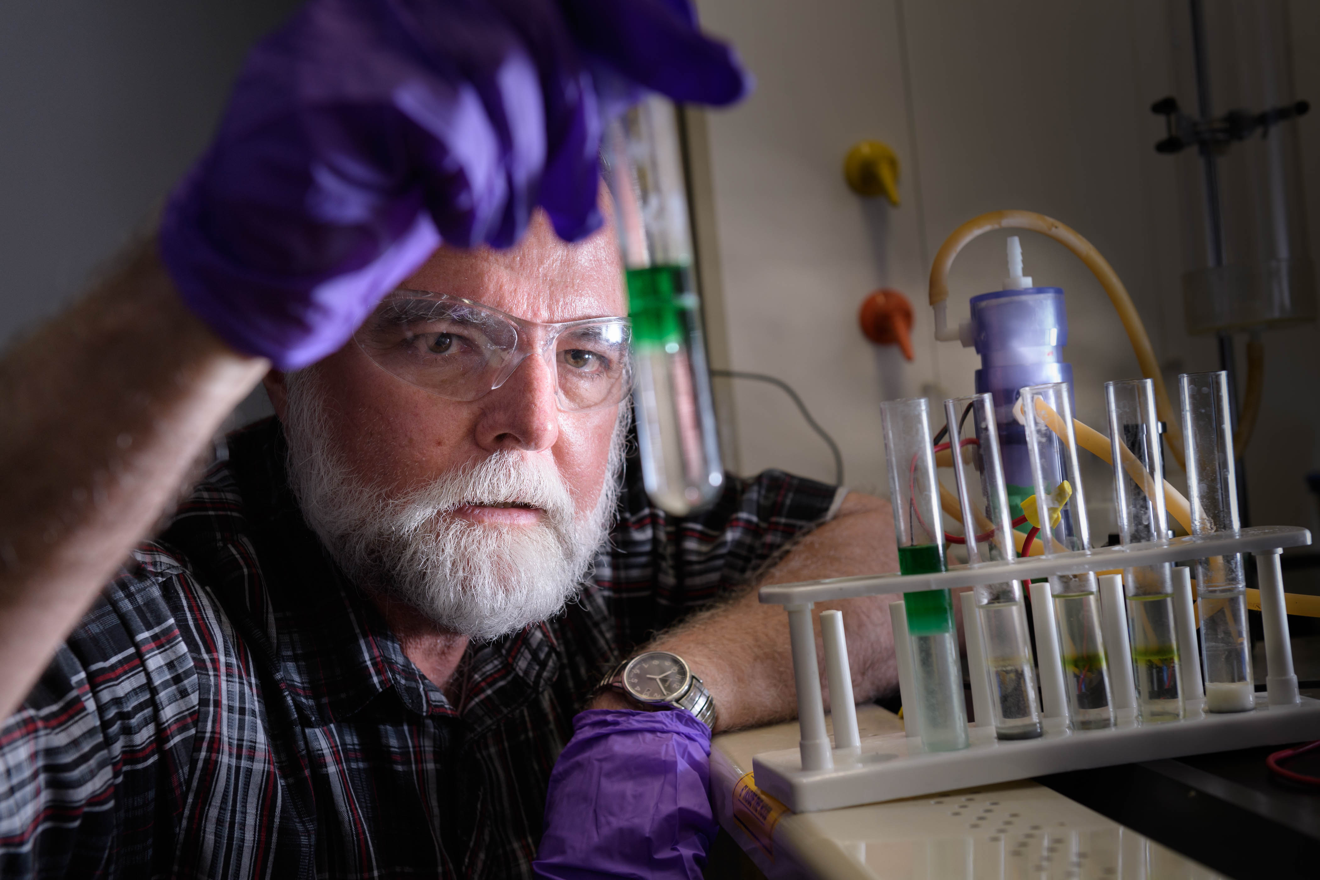 Man holding test tube with flow battery in background (© Purdue Research Foundation)