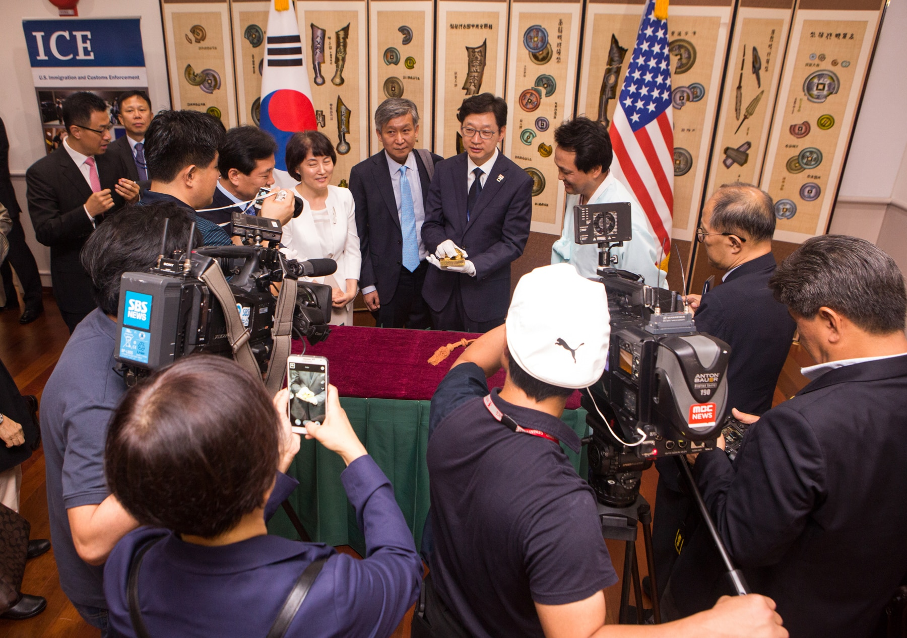 Press conference with speaker holding carved seal (State Dept./D.A. Peterson)