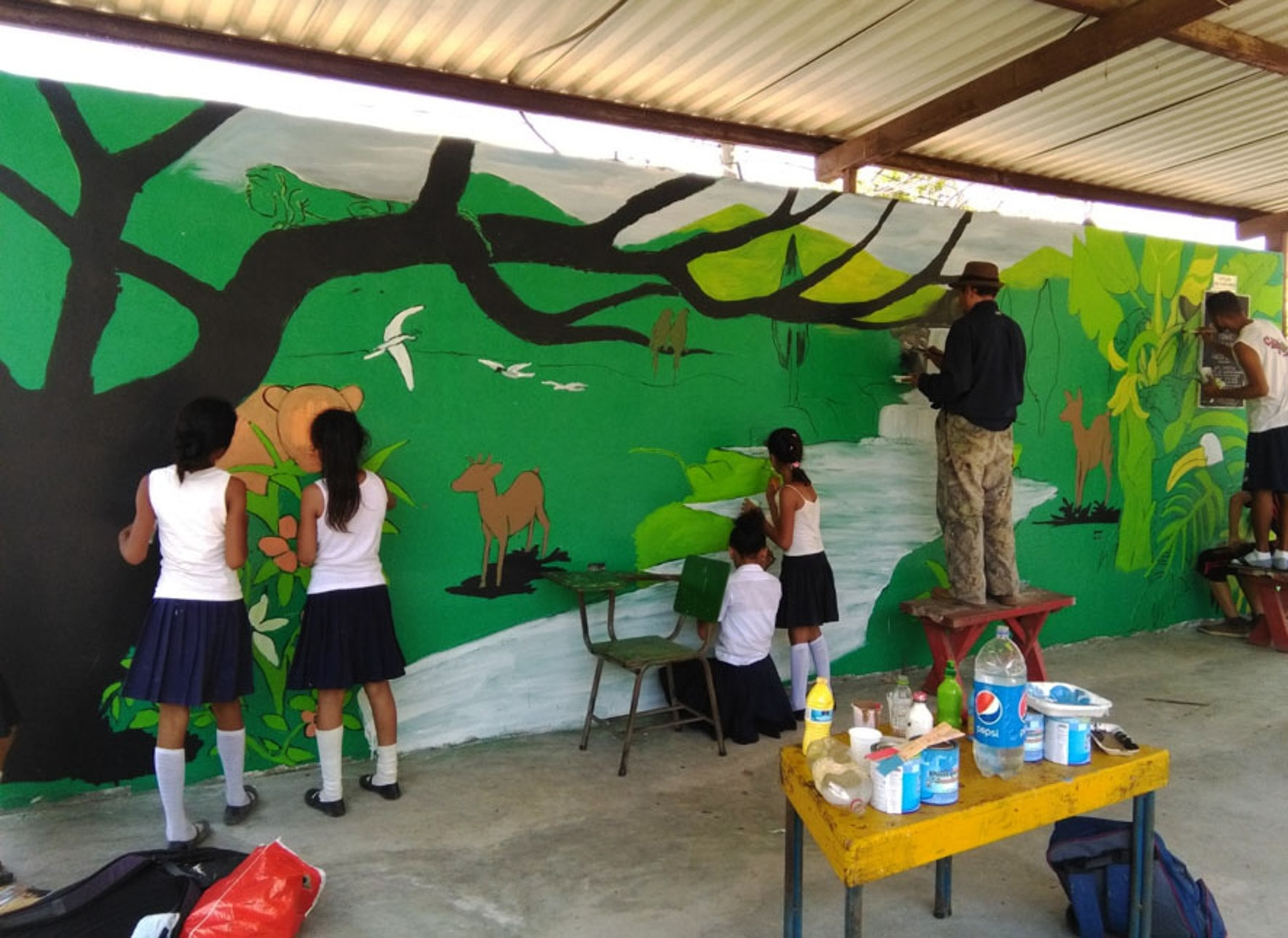 Adults and children painting mural on wall (U.S. Embassy Tegucigalpa/David Dulko)