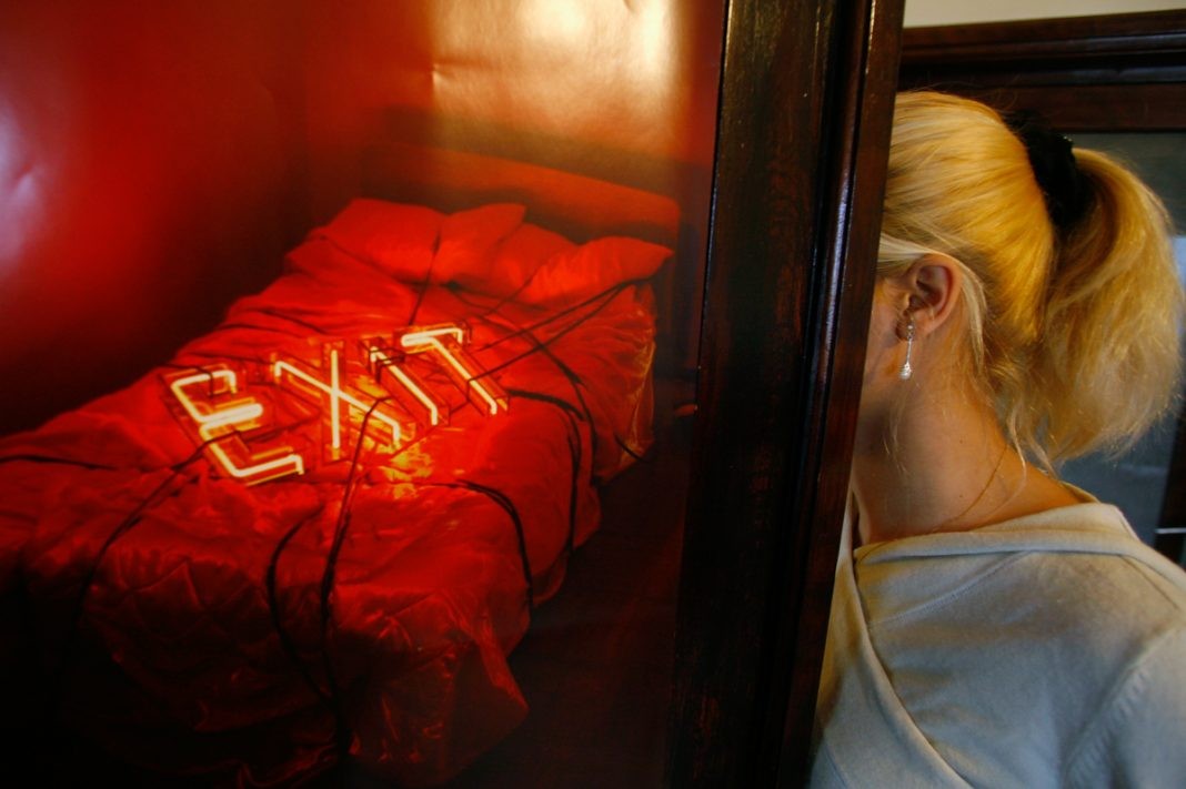 Red bed with exit sign and woman near it (© Bogdan Cristel/Reuters)