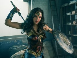 Wonder Woman holding shield and removing sword from scabbard (© 2017 Warner Bros./Clay Enos)