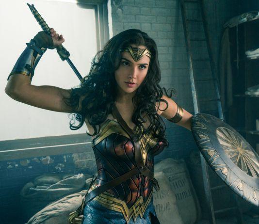 Mulher Maravilha segurando o escudo e removendo a espada da bainha (© 2017 Warner Bros./Clay Enos)