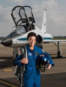 Jessica Watkins in flight suit and in front of jet (NASA)