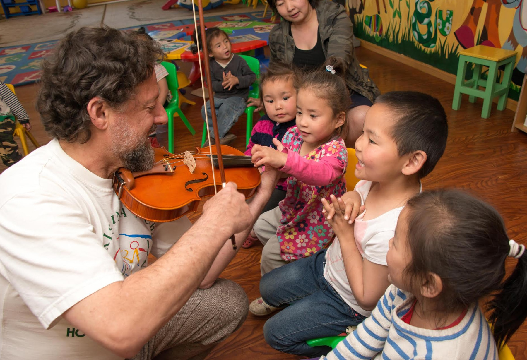 Violinist showing orphans his instrument (Jan Regan/Philadelphia Orchestra)