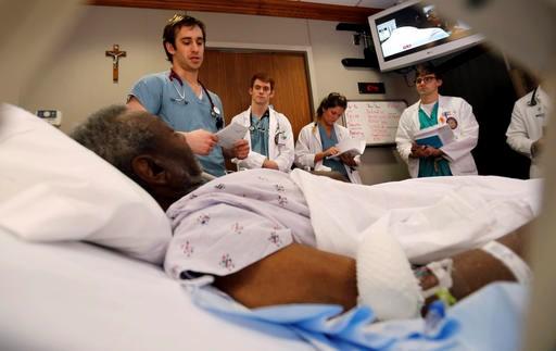 路易斯安那州圣母湖地区医疗中心的住院医生卡梅伦·科利尔带领实习医生及医学院学生为患者做检查(照片:美联社)