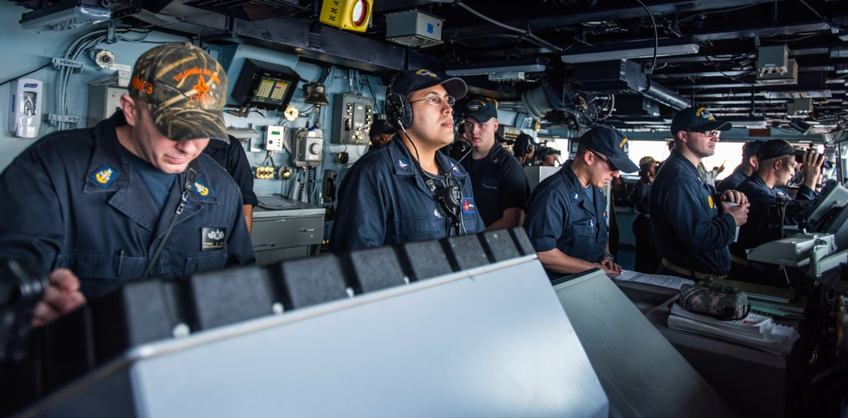 Row of people standing at naval vessel controls (DOD/U.S. Navy Petty Officer 2nd Class Christopher Gaines)