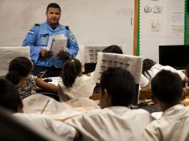 Police officer standing in front of classroom of students (U.S. Embassy Tegucigalpa)