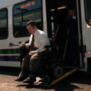وہیل چیئر میں بیٹھا آدمی بس سے نیچے اتر رہا ہے (© Jeffrey Haderthauer/AP Images)