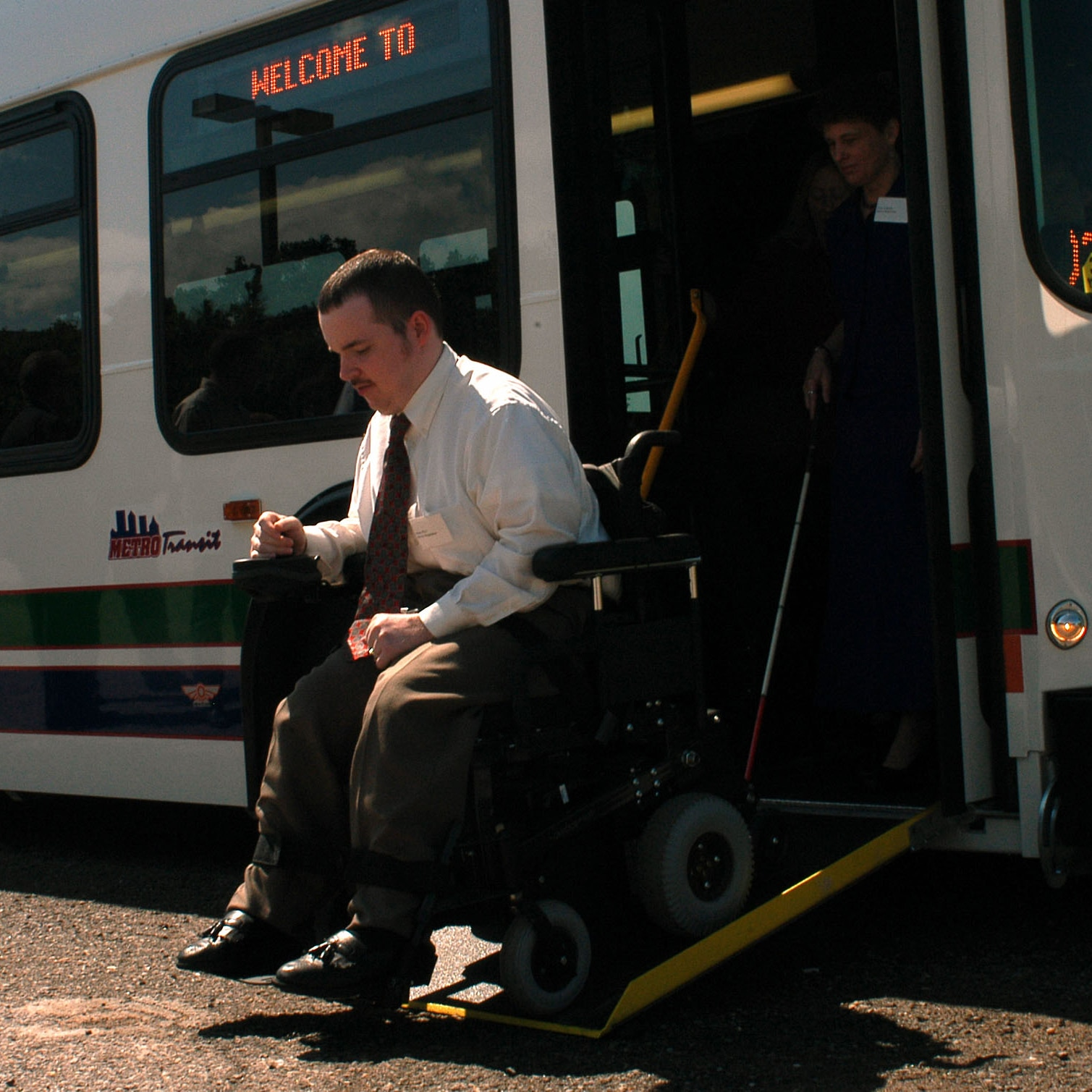 Man in wheelchair disembarking a bus (© Jeffrey Haderthauer/AP Images)