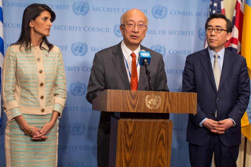 Three people speaking from podium (© AP Images)