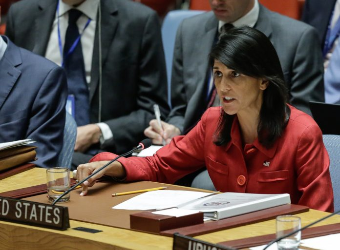 Nikki Haley seated at desk and speaking (© AP Images)