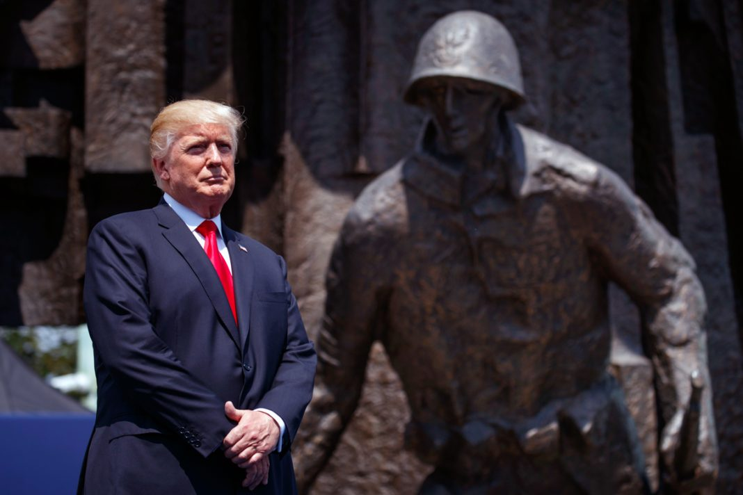President Trump standing next to statue of soldier (© AP Images)