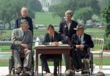 George H.W. Bush signing document as others look on, with two in wheelchairs (© Barry Thumma/AP Images)