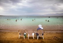 Boy sitting in one of three chairs while others swim in Dead Sea (© AP Images)