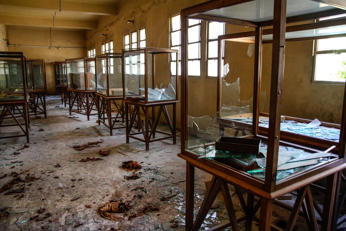 Une salle remplie de vitrines vides, cassées, avec des morceaux de verre jonchant le sol (© AP Images)