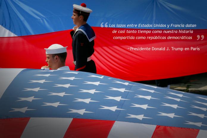 Marineros estadounidenses y franceses de pie junto a grandes banderas de Estados Unidos y Francia (© AP Images)
