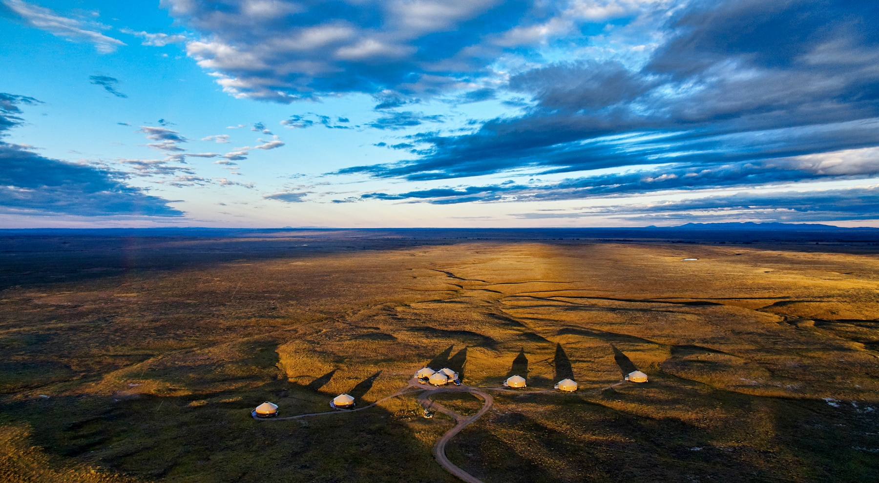 Bird's-eye view of a group of tents on open prairie at sunset (Gib Myers/APR)