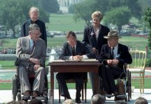 People watching President George H.W. Bush signing document (© AP Images)