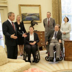 وہیل چیئروں میں بیٹھے ہوئے دو اور کھڑے ہوئے تین آدمیوں  سے جارج ڈبلیو بش باتیں کر رہے ہیں (© Eric Draper/White House/AP Images)