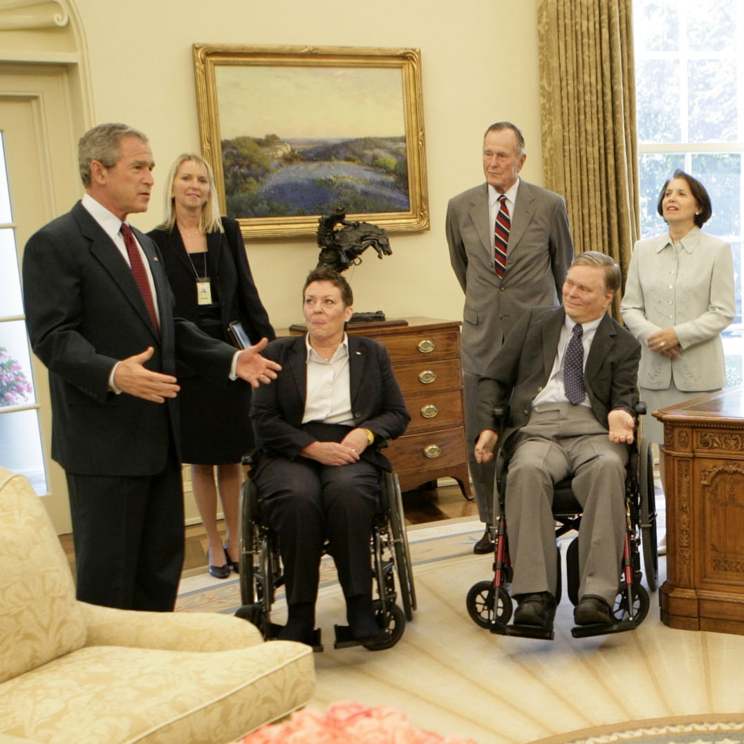 George W. Bush speaking to two people in wheelchairs and three others standing (© Eric Draper/White House/AP Images)