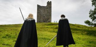 Two men holding swords, dressed in capes, walking toward castle (© Getty Images)