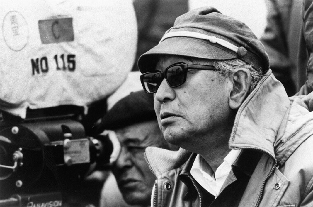 Homem usa chapéu e óculos escuros ao lado de outro homem que olha através da lente de uma câmera de filmar (© AFP/Getty)