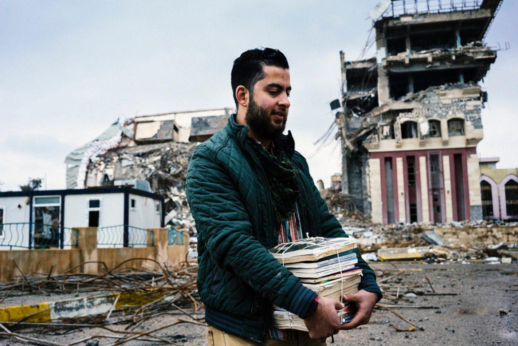 Hombre cargando libros frente a edificios destruidos por la guerra (© Dimitar Dilkoff/AFP/Getty)